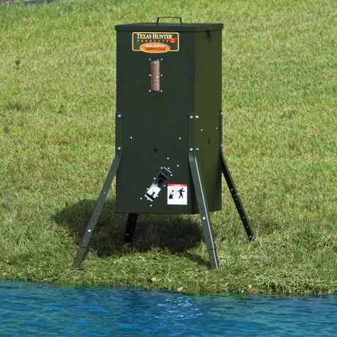 A Texas Hunter Products brand automatic fish feeder next to a pond
